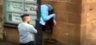 醉酒女子折叠身体卡在灯柱与墙壁之间